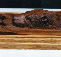 Otter and frog meet nose to nose. Carved in walnut with an oak base.